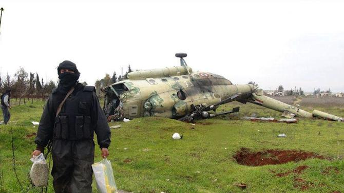 This citizen journalism image provided by Edlib News Network, ENN, which has been authenticated based on its contents and other AP reporting, shows a Syrian rebel carrying food supplies, as he walks in front of a  damaged helicopter at Taftanaz air base that was captured by the rebels, in Idlib province, northern Syria, Friday Jan. 11, 2013. Islamic militants seeking to topple President Bashar Assad took full control of a strategic northwestern air base Friday in a significant blow to government forces, seizing helicopters, tanks and multiple rocket launchers, activists said. (AP Photo/Edlib News Network ENN)