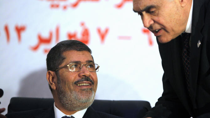 Egyptian President Mohammed Morsi smiles as he listens to his Foreign Minister Mohammed Kamel Amr during the opening of the 12th summit of the Organization of Islamic Cooperation in Cairo, Egypt, Wednesday, Feb. 6, 2013. Egypt's president took a break from mounting domestic troubles Wednesday to host an Islamic summit that has, even before starting, laid bare divisions within the Muslim world. Morsi opened the two-day summit a day after after his central bank reported another alarming drop in foreign currency reserves.(AP Photo/Amr Nabil)