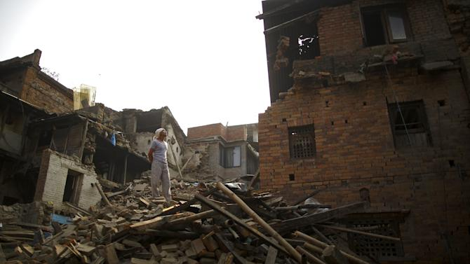 A man stands on top of a collapsed house after the April 25 earthquake at Bhaktapur