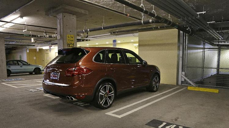 A Porsche SUV is parked in space #142 Thursday, June 13, 2013, in a parking lot near AT& T Park in San Francisco. A spot in the city's trendy South Beach neighborhood sold last week for $82,000. The 8- by 12-foot parking space is in an enclosed garage in a condominium building. While it may seem like a lot of money, real estate agents say parking could be a good investment. It can add as much as $100,000 to the purchase price of a property, or be rented out at rates of $400 to $450 a month, the going rate in South Beach. (AP Photo/Ben Margot)