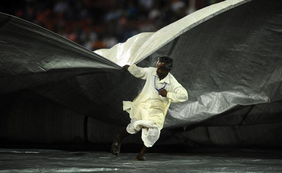 A groundsman pulls the covers as the IPL