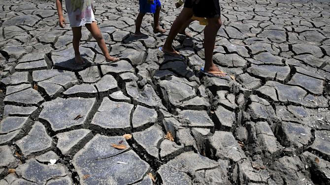 Residents walk over cracked soil of a 1.5 hectare dried up fishery at the Novaleta town in Cavite province, south of Manila