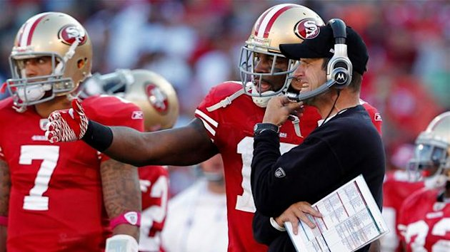 AMERICAN FOOTBALL NFL San Francisco 49ers head coach Jim Harbaugh (R) talks with wide receiver Braylon Edwards (2nd R) during the fourth quarter of their NFL football game against the Cleveland Browns in San Francisco, California, October 30, 2011.