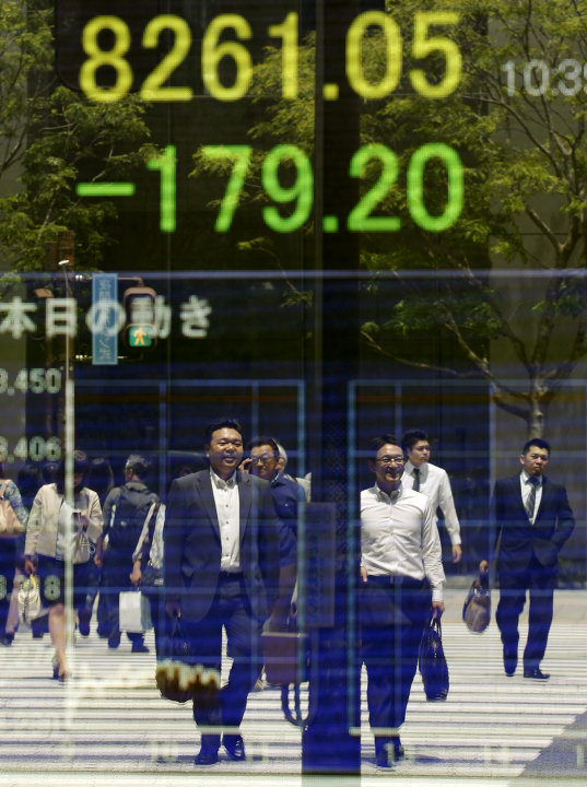 People are reflected on the electronic board of a securities firm in Tokyo, Monday, June 4, 2012. Asia stock markets took a beating Monday as signs that the U.S. economic recovery might be shifting in
