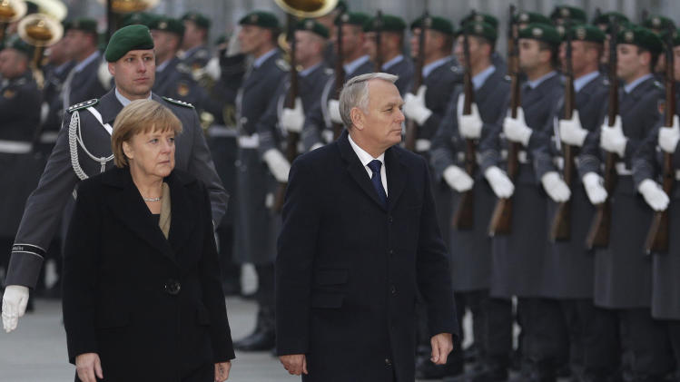 German Chancellor Angela Merkel, left, welcomes Prime Minister of France, Jean-Marc Ayrault, right, with military honors in front of the chancellery in Berlin, Germany, Thursday, Nov. 15, 2012. (AP Photo/Michael Sohn)