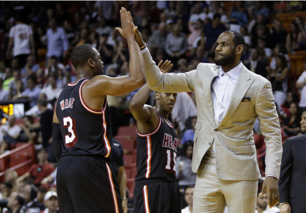 Miami Heat's LeBron James, right, high-fives Dwyane Wade (3) during a time out in the second half of an NBA basketball game against the Chicago Bulls, Sunday, Feb. 23, 2014, in Miami. The Heat def