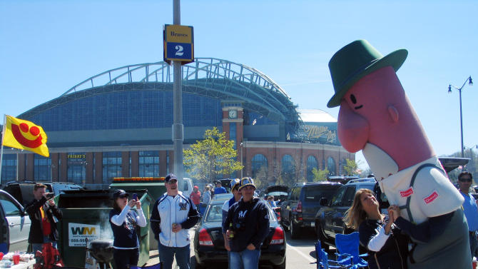 A Milwaukee Brewers fan dances with Brat, one of the five popular Racing Sausages that are fan favorites at Miller Park, Friday, April 6, 2012, before the season opener baseball game against the St. Louis Cardinals in Milwaukee. A Good Friday home opener posed a spiritual dilemma for some Catholic baseball fans in Milwaukee, who had to decide whether to abstain from eating meat as their religion dictates or to indulge in one of Brewers' fans most cherished traditions. (AP Photo/Dinesh Ramde)
