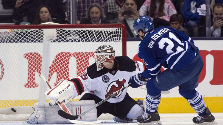 Toronto Maple Leafs left winger James van Riemsdyk scores the game winning shootout goal on New Jersey Devils goaltender Cory Schneider during an NHL hockey game, Friday, Nov. 8, 2013 in Toronto