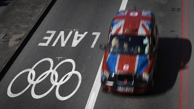 A taxi passes alongside one of the official Olympic Lanes on a street in central London Monday, July 23, 2012, ahead of the 2012 Summer Olympics. (AP Photo/Ben Curtis)
