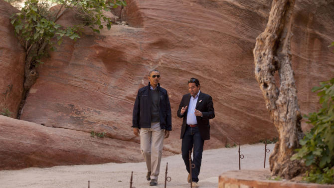 U.S. President Barack Obama walks with Dr. Suleiman A. D. Al Farajat, right, a tourism professor with the University of Jordan, through the Siq during a visit to the ancient city of Petra, in south Jordan, Saturday, March 23, 2013. (AP Photo/Carolyn Kaster)