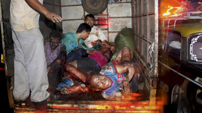 EDS NOTE: GRAPHIC CONTENT -- Injured victims of a bomb explosion are loaded onto a truck to be taken to hospital, at Zaveri bazar in Mumbai, India, Wednesday, July 13, 2011. Three explosions hit busy locations late Wednesday in India's business capital of Mumbai, where a terror siege nearly three years ago killed 166 people. (AP Photo)