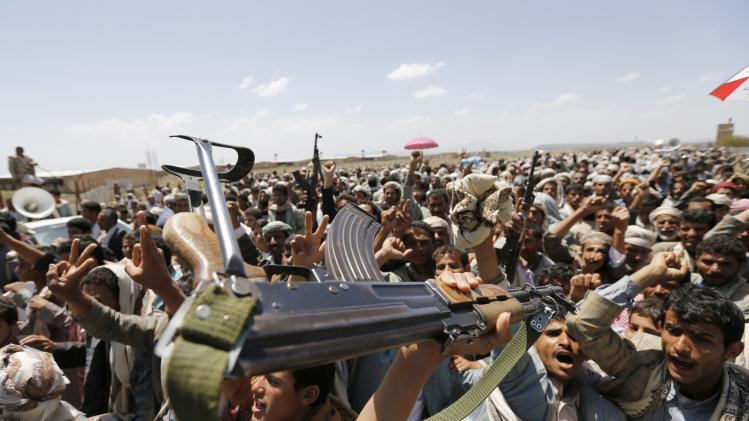 A follower of the Shi'ite Houthi group brandishes his rifle during a gathering near Sanaa