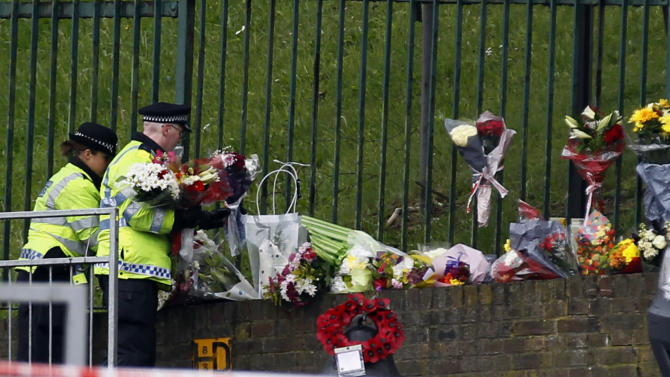 Police officers lay down floral tributes handed to them by members of the public at the scene of a terror attack in Woolwich, southeast London, Thursday, May 23, 2013.  The British government's emergency committee met Thursday after two attackers killed a man in a daylight attack in London that raised fears terrorism had returned to the capital. (AP Photo/Sang Tan)