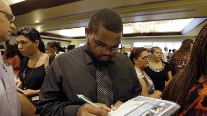 FILE - In this Wednesday, Aug., 14, 2013, file photo, job seeker Kelsey Devoe, of Miramar, Fla., fills out a contact form at a job fair in Miami Lakes, Fla. The Labor Department reports on the number of Americans who applied for unemployment benefits for the third week of September on Thursday, Sept. 19, 2013. (AP Photo/Alan Diaz, File)