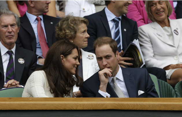 Britain's Prince William, right, and his wife Kate, Duchess of Cambridge, left, speak to each other ahead of a quarterfinals match between Roger Federer of Switzerland and Mikhail Youzhny of Russia at