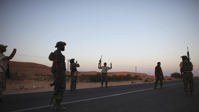 "Former rebel fighters celebrate after allegedly capturing a Grad multiple rocket launcher system, at a checkpoint near Bani-Walid, Libya, Monday, Sept. 12, 2011. Three weeks after the fall of Tripoli appeared to herald the end of Libya's brutal war, the protracted battle over the loyalist bastions of Bani Walid and Sirte, Gadhafi's hometown, has dashed hopes of a speedy ""declaration of liberation"" that would start the clock ticking on a transition to democracy. (AP Photo/Alexandre Meneghini)"