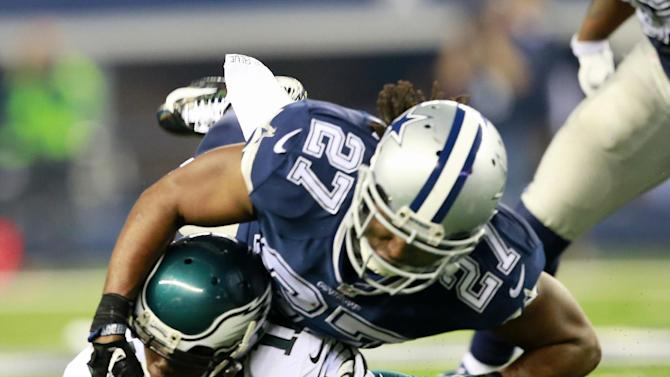 Philadelphia Eagles wide receiver Josh Huff (11) is tackled by Dallas Cowboys free safety J.J. Wilcox (27) during the second half of an NFL football game Thursday, Nov. 27, 2014, in Arlington, Texas