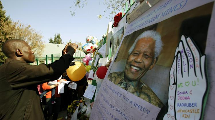 Unidentified man takes a photograph of picture former South African President Nelson Mandela and well-wishers message outside the Mediclinic Heart Hospital where is being treated in Pretoria, South Africa Sunday, June 30, 2013. South Africans in Sunday services have been praying for former President Nelson Mandela who is spending his 23rd day in a Pretoria hospital in critical condition. (AP Photo/Themba Hadebe)