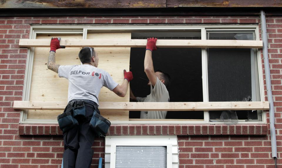 Workers with Belfor Property Restoration work to board up a window in the apartment of suspected Aurora movie theater gunman James Holmes, Wednesday, July 25, 2012, as residents were allowed back in the building, which had been closed off by police due to the continuing investigation of the shooting. (AP Photo/Ted S. Warren)
