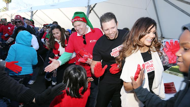 "IMAGE DISTRIBUTED FOR MATTEL - From right, WWE stars Diva Eve and The Miz, Bryan Stockton, Mattel CEO, and Deidre Lind, Executive Director, Mattel Children's Foundation, greet Los Angeles school children at Mattel's Southern California headquarters for a ""Winter Wonderland"" featuring 220 tons of snow on Thurs., Dec. 13, 2012 in El Segundo, Calif. (Photo by Casey Rodgers/Invision for Mattel/AP Images)"