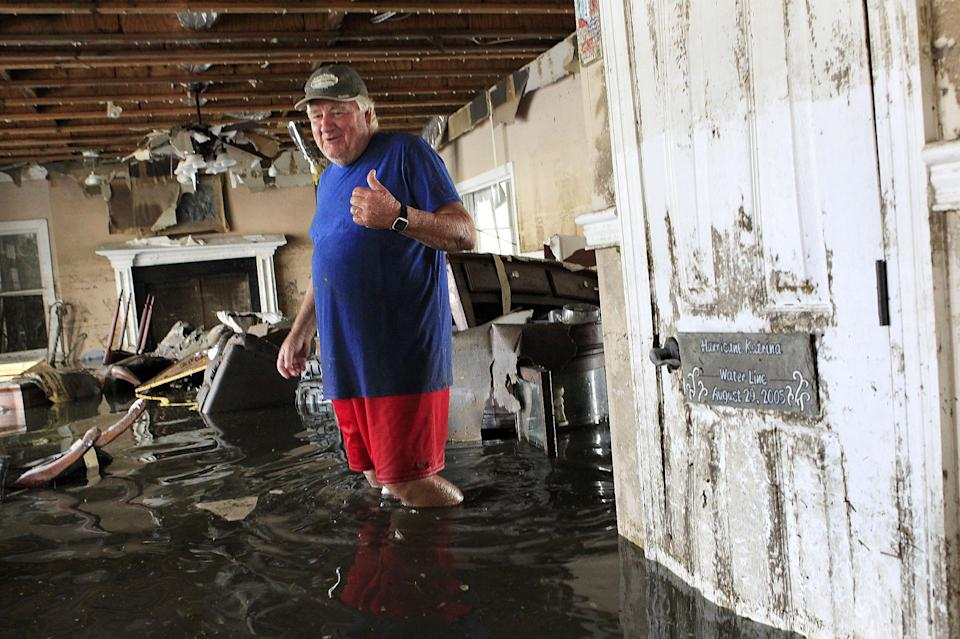 Don Duplantier walks through his flooded home as water recedes from Hurricane Isaac in Braithwaite, La., Sunday, Sept. 2, 2012. In the foreground, is a sign marking the waterline from Hurricane Katrina, but floodwater from Isaac went all the way to the second floor. (AP Photo/Gerald Herbert)