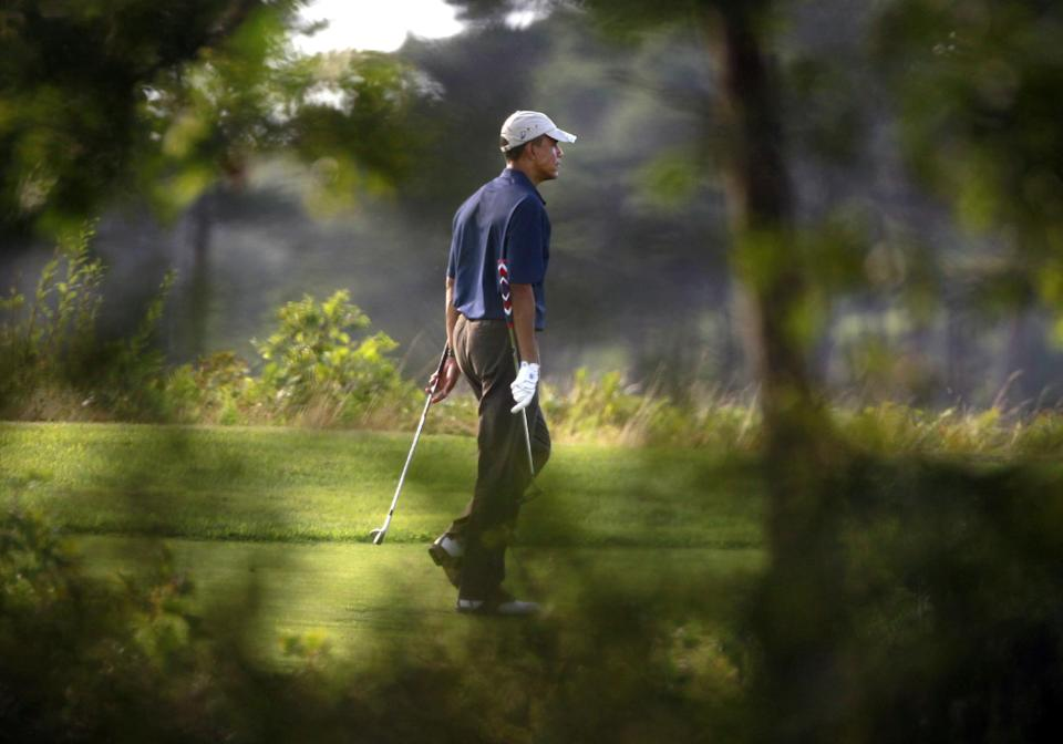 In this photo taken Friday, Aug. 19, 2011, President Barack Obama walks along a fairway at the Vineyard Golf Club while playing golf in Edgartown, Mass., on the island of Martha's Vineyard.  Obama is vacationing on the island with his family during the last half of August 2011. (AP Photo/Steven Senne)