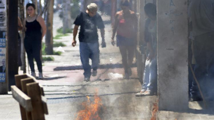 People walk behind a burning barricade during a police strike in Cordoba