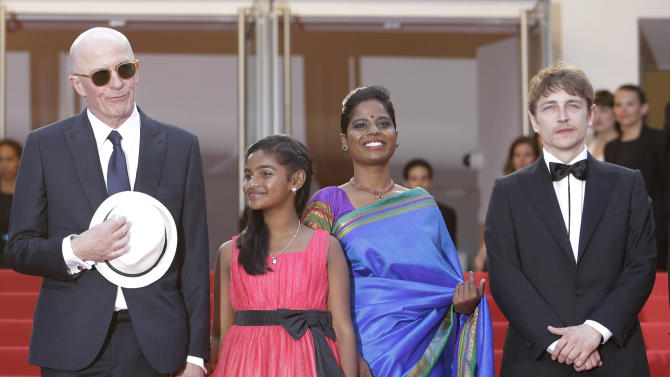 From left, Jesuthasan Antonythasan, director Jacques Audiard, Claudine Vinasithamby and Kalieaswari Srinivasan pose for photographers upon arrival for the screening of the film Dheepan at the 68th international film festival, Cannes, southern France, Thursday, May 21, 2015. (AP Photo/Lionel Cironneau)