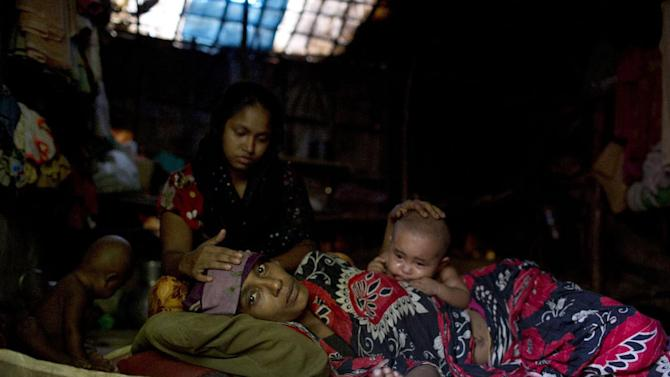 In this Thursday, May 21, 2015 photo, Musammat Shahida, top, a Rohingya from Myanmar, takes care of her sister Musammat Somuda suffering from fever at a camp for Rohingya people in Ukhiya, near Cox's Bazar, a southern coastal district about, 296 kilometers (183 miles) south of Dhaka, Bangladesh. As a boat people crisis emerged in Southeast Asia in recent weeks, nearly all the focus has been on the Rohingya: the persecuted Muslim minority fleeing Myanmar. But of the more than 3,000 people who have come ashore this month in Indonesia, Malaysia and Thailand, about half were from Bangladesh, according to the U.N. refugee agency, mainly poor laborers seeking better jobs and a brighter future. (AP Photo/A.M. Ahad)