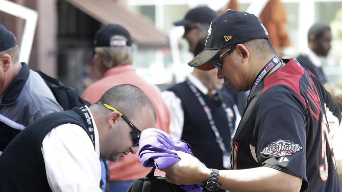 In this photo taken Wednesday, April 24, 2013, a security guard checks the backpack of a fan entering AT&T Park before a baseball game between the San Francisco Giants and the Arizona Diamondbacks in San Francisco. Major League Baseball's previously scheduled security meeting in New York took on added importance in the aftermath of the marathon bombs. Each team sets its own security standards, although clubs might consider cutting the size of the general major league limitation on bags from 16x16x8 inches to something less.(AP Photo/Jeff Chiu)