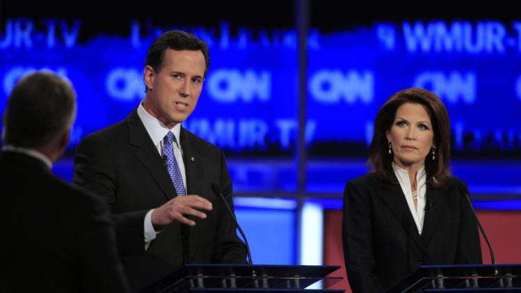 Former Pennsylvania Sen. Rick Santorum, center, answers a question asked by CNN's John King, left, as Rep. Michele Bachmann, R-Minn., right, listens during the first New Hampshire Republican presidential debate at St. Anselm College in Manchester, N.H., Monday, June 13, 2011. (AP Photo/Jim Cole)