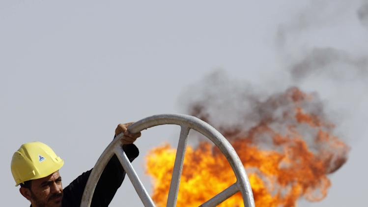 FILE - In this file photo of Friday, July 17, 2009, an Iraqi worker operates valves at the Nahran Omar oil refinery near the city of Basra, 340 miles (550 kilometers) southeast of Baghdad, Iraq. The International Energy Agency predicted Tuesday Oct. 9, 2012 that Iraq will consolidate its position as a global oil power _ allowing it to rebuild the economy of a nation ravaged by war and decades of Saddam Hussein's autocratic rule.  The leading global energy monitor reported that Iraq's annual revenues from energy exports could double to an average of $200 billion annually over the next 20 years. That optimistic scenario would make Iraq's economy the same size as that of Saudi Arabia now by 2035. (AP Photo/Nabil al-Jurani, File)