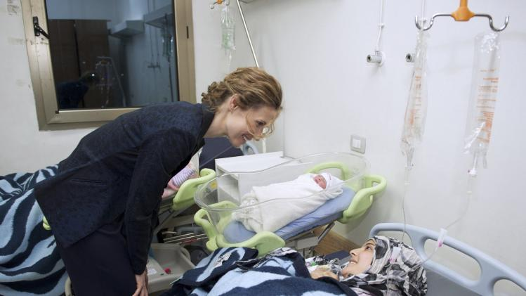 Handout showing Asma al-Assad talking to a patient during her visit to the Obstetrics hospital in Damascus