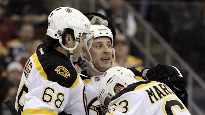 Boston Bruins center Gregory Campbell, center, is congratulated by teammates Jaromir Jagr, left, of the Czech Republic, and Brad Marchand after scoring a goal against the New Jersey Devils during the first period of an NHL hockey game on Wednesday, April 10, 2013, in Newark, N.J. (AP Photo/Julio Cortez)