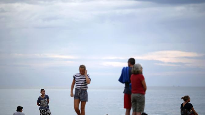 People attending a Swedish memorial service for victims of 2004 tsunami are seen at a beach in Khao Lak