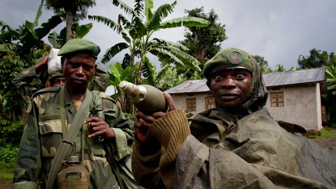 FILE - In this May 17, 2012 file photo, a Congolese government army soldier displays a mortar round after his unit returned from fighting against rebel forces, in Kinyamahura, Congo. Gold is now the primary source of income for armed groups in eastern Congo, and is ending up in jewelry stores across the world, according to a report published Thursday, Oct. 25, 2012, by the Enough Project. Following American legislation requiring companies to track the origin of the minerals they use, armed groups have been unable to profit from the exploitation of tin, tungsten, and tantalum, and have turned instead to gold, which is easier to smuggle across borders. (AP Photo/Marc Hofer, File)