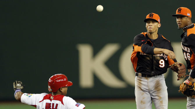 Netherlands' shortstop Andrelton Simmons (9) throws first for a double play as Cuba's rightfielder Alexei Bell slide into second in the third inning of their World Baseball Classic second round game in Tokyo Friday, March 8, 2013. (AP Photo/Koji Sasahara)