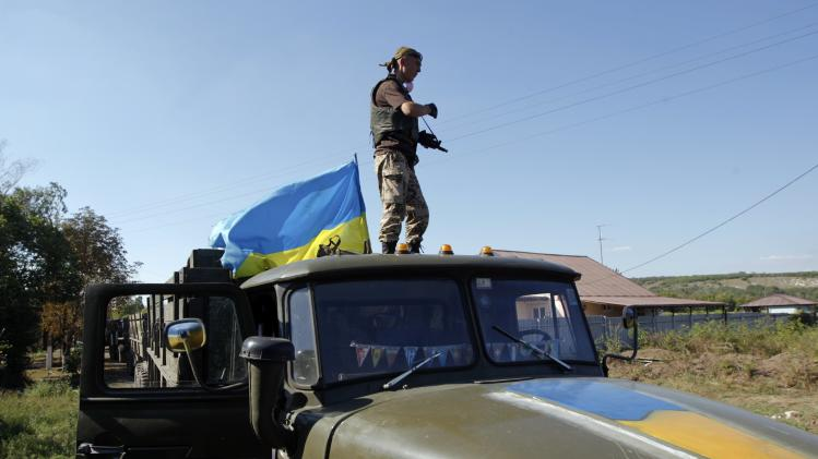 A Ukrainian serviceman stands on a military truck as he mans a checkpoint in Luhansk region