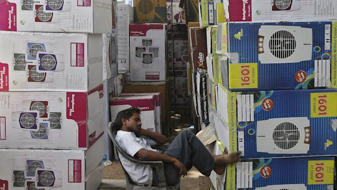 A vendor sleeps next to stacked cartons of air coolers kept for sale at a shop on a hot summer day in New Delhi