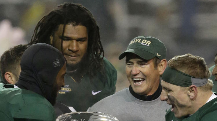 Baylor head coach Art Briles, center right, celebrates with players Ahmad Dixon, left, Cyril Richardson, center left,  and Eddie Lackey (5) with the Big 12 trophy after their NCAA college football game against Texas, Saturday, Dec. 7, 2013, in Waco, Texas. Baylor won 30-10 to clinch the title