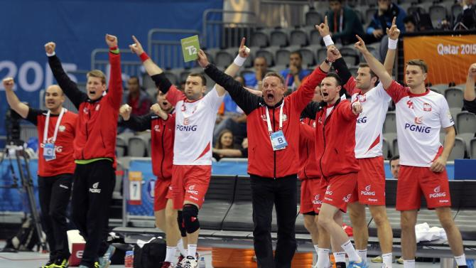 Coach Biegler of Poland and players celebrate a goal against Poland during the round of 16 match of the 24th men's handball World Championship in Doha
