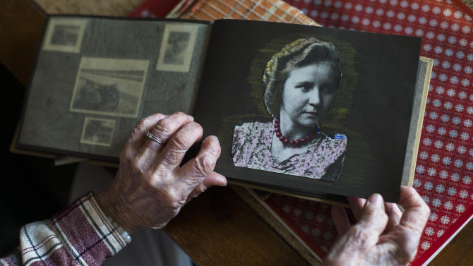 """Margot Woelk, one of the food testers of Adolf Hitler, shows an old photo album with a picture of herself taken around 1939 or 1940, during an interview with The Associated Press in Berlin, Thursday, April 25, 2013. Margot Woelk was one of 15 young women who sampled Hitler's food to make sure it wasn't poisoned before it was served to the Nazi leader in his """"Wolf's Lair,"""" the heavily guarded command center in what is now Poland, where he spent much of his time in the final years of World War II. Margot Woelk kept her secret hidden from the world, even from her husband then, a few months after her 95th birthday, she revealed the truth about her wartime role. (AP Photo/Markus Schreiber)"""