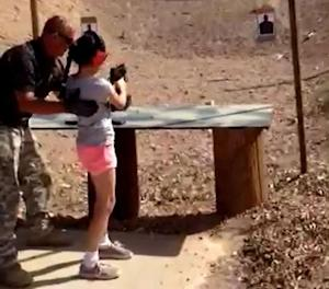 Shooting instructor Charles Vacca stands next to a 9-year-old girl at the Last Stop shooting range in White Hills
