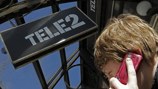 A man talks on a telephone outside a branch of Nordic telecoms group Tele2 in St. Petersburg