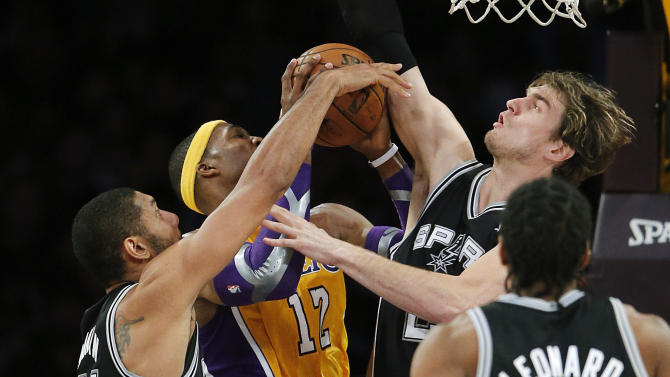 Los Angeles Lakers' Dwight Howard, center, is defended by San Antonio Spurs' Tim Duncan, left, and Tiago Splitter, of Brazil, in the first half of an NBA basketball game in Los Angeles, Tuesday, Nov. 13, 2012. (AP Photo/Jae C. Hong)