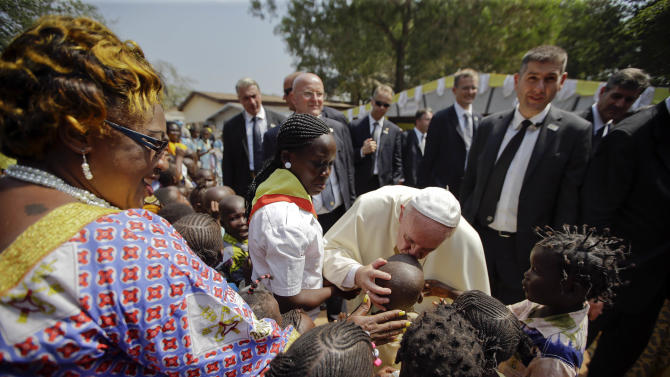 Pope Francis blesses children during his visit at a refugee camp, in Bangui, Central African Republic, Sunday, Nov. 29, 2015. The Pope has landed in the capital of Central African Republic, his final stop in Africa and where he will seek to heal a country wracked by conflict between Muslims and Christians. (AP Photo/Andrew Medichini)