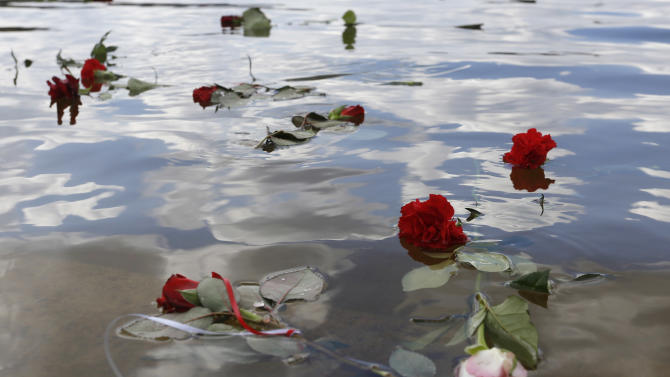 Flowers float in a lake after an event at the former Nazi concentration camp Ravensbrueck in Fuerstenberg, northeastern Germany, Sunday, April 19, 2015 to commemorate the  70th anniversary of the liberation of the camp by the Red Army on April 30, 1945.  (AP Photo/Ferdinand Ostrop)