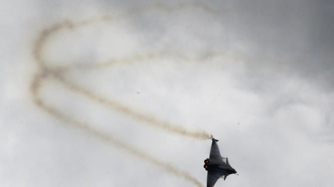 A French Air Force Rafale fighter performs its demonstration flight during the 50th Paris Air Show at Le Bourget airport, north of Paris, Friday, June 21, 2013. (AP Photo/Francois Mori)