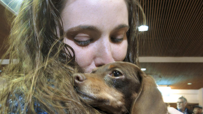 Mandi Smith, of Fort Campbell, Ky., is reunited with her dog, Pooka, Wednesday, Jan. 30, 2013 at the Albuquerque International Sunport Airport in Albuquerque, N.M.  The Chihuahua-dachshund mix, also known as a chiweenie, disappeared from her yard 18 months ago and was found wandering the streets 1,200 miles away in Espanola, N.M., in January. The dog was traced to Smith by her microchip, but how she got to New Mexico is a mystery. (AP Photo/Jeri Clausing)