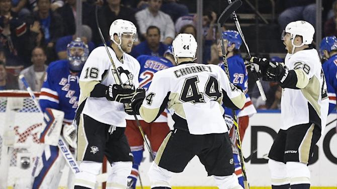 Pittsburgh Penguins' Ian Cole (28) and Taylor Chorney (44) celebrate with teammate Brandon Sutter after Sutter scored a goal against New York Rangers goalie Henrik Lundqvist, back left, during the second period of Game 2 in the first round of the NHL hockey Stanley Cup playoffs Saturday, April 18, 2015, in New York. (AP Photo/Frank Franklin II)